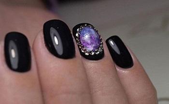 Чёрный маникюр с украшением в виде жидких камней на безымянном пальце